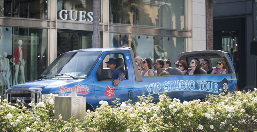 Tourists drive down Rodeo Drive in a tour bus.