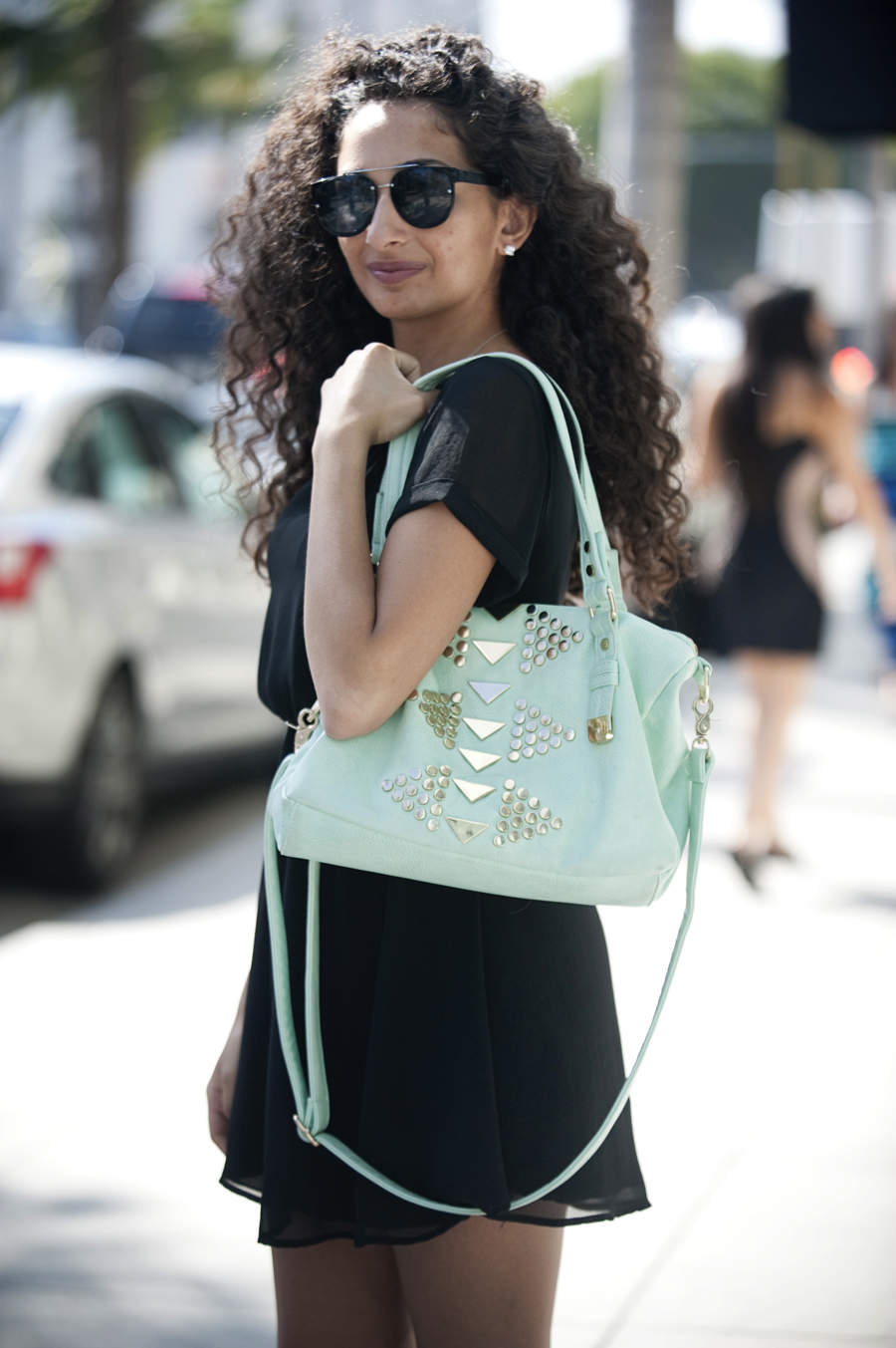 Dominique Aghassai, 21, wears a mint handbag from Shii and a black dress from Nordstrom.