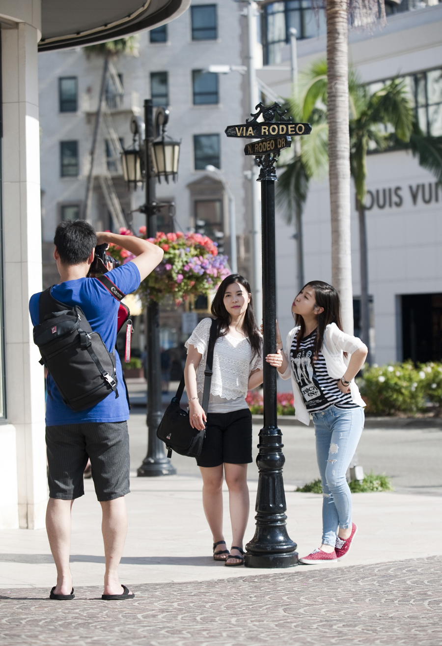 Lee Soo Jin and Yu Ji Suk, visiting from Seoul, get their photographs taken on Rodeo Drive by a friend.