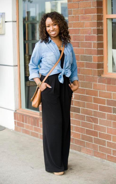 Chanelle Bruce, 36, in Laguna Beach wearing a black gaucho jumpsuit, a chambray shirt tied in the front, wedge sandals and a Fossil cross body bag.
